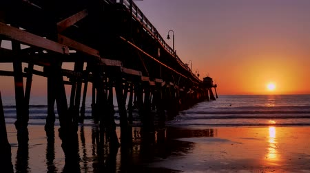 Scenic orange pink Sunset with epic rays of light and sun flare wooden pier in San Clementa California Стоковые видеозаписи