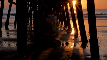 Slow tilt under the pier Scenic orange pink Sunset with epic rays of light and sun flare wooden pier in San Clementa California Стоковые видеозаписи