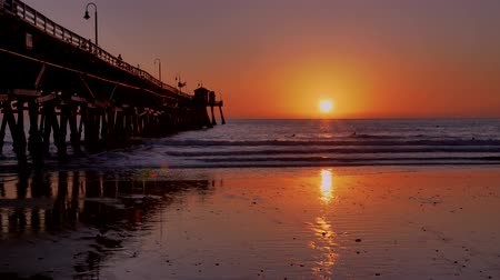 западный : Scenic orange pink Sunset with epic rays of light and sun flare wooden pier in San Clementa California Стоковые видеозаписи
