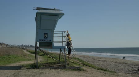 megye : Woman standing at lifeguard tower and waving at summer day . Travel Vacation Retirement Lifestyle Concept California Orange county San clemente