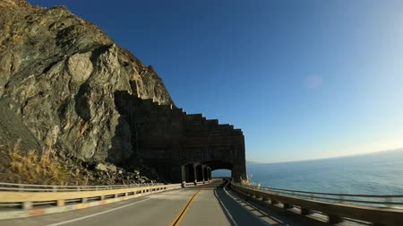 západ : Scenic road Driving thru tunnel arches Rain Rocks Rock Shed and Pitkins Curve Highway 1 coast road Big Sur California USA Dostupné videozáznamy