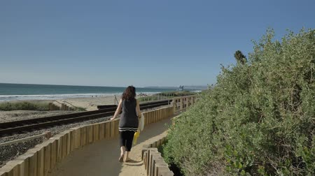 Active Senior woman walking at pedestrian trail wooden bridge close to rails ocean with beautiful landscapes at summer day in california san clemente calafia beach. orange county lifestyle