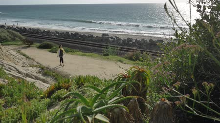 Active Senior woman walking at pedestrian trail close to ocean with beautiful landscapes at summer day in california san clemente calafia beach. orange county lifestyle surfer in bacground