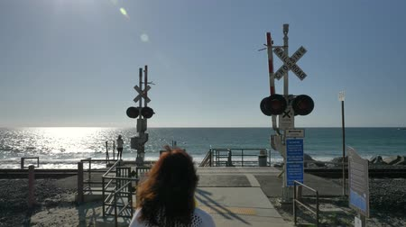 Active Senior woman cross railroad close to ocean with beautiful landscapes at summer day in california san clemente calafia beach. orange county lifestyle