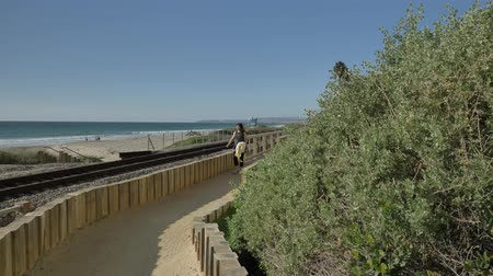 Active Senior woman walking at pedestrian trail wooden bridge close to ocean with beautiful landscapes at summer day in california san clemente calafia beach. orange county lifestyle