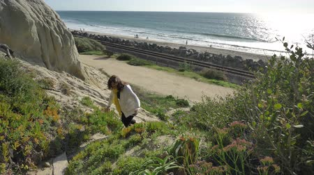 Active Senior woman walking at pedestrian trail close to ocean with beautiful landscapes at summer day in california san clemente calafia beach. orange county lifestyle Стоковые видеозаписи