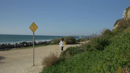 Active Senior woman walking at pedestrian trail close to ocean with beautiful landscapes at summer day in california san clemente calafia beach. orange county lifestyle Stock Footage