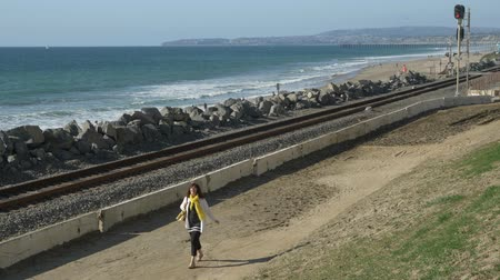 egyetlen virág : Active Senior woman walking at pedestrian trail close to ocean with beautiful landscapes at summer day in california san clemente calafia beach. orange county lifestyle Stock mozgókép