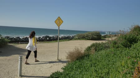 egyetlen virág : Active Senior woman walking at pedestrian trail close to ocean with beautiful landscapes at summer day in california san clemente calafia beach. orange county lifestyle pan left