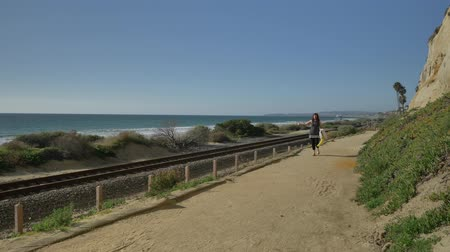 egyetlen virág : Active Senior woman walking wave at pedestrian trail close to ocean with beautiful landscapes at summer day in california san clemente calafia beach. orange county lifestyle