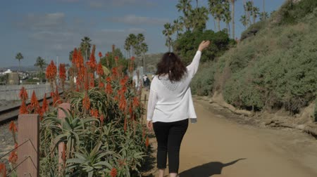 egyetlen virág : Active Senior woman waving to somebody at pedestrian trail close to ocean with beautiful landscapes at summer day in california san clemente calafia beach. orange county lifestyle