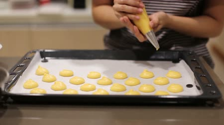 Woman chef with confectionery bag squeezing choux cream on a tray.