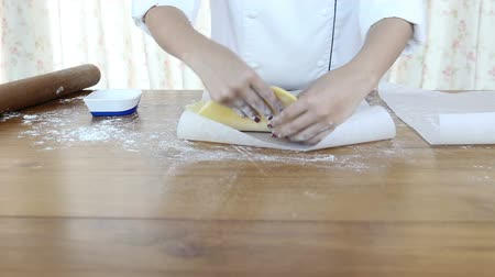 Woman rolls dough on the table with a rolling pin. Wideo