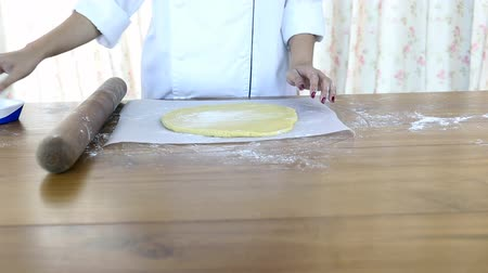 дрожжи : Woman rolls dough on the table with a rolling pin. Стоковые видеозаписи