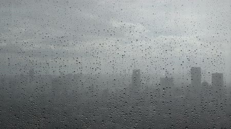 Rain water drop on window glass with city in background.