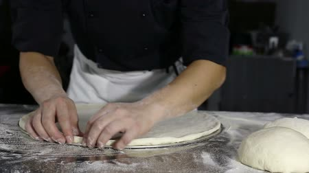 Chef forming the dough on a floured surface and kneading it with his hands. Wideo
