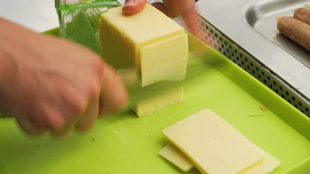 cheddar : Knife cutting slices of cheddar cheese for a BBQ Stock Footage