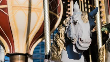 sela : White horse with yellow saddle on a french merry-go-round, zoom in