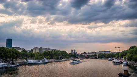 boat tour : Timelapse of boats in Paris in front of Jussieu University, with a threatening cloudy and stormy sky, view from Austerlitz bridge