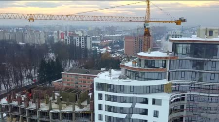 Aerial view of high modern residential building and tower crane under construction.