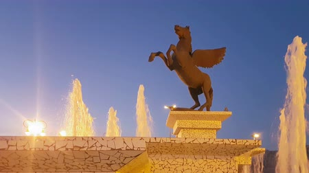 pegaz : Corinth, Greece, 5 October 2017. Night hour of Pegasus statue in Corinth in Greece against the fountain. A beautiful scenic.