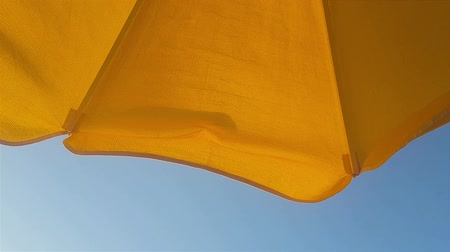 Beach yellowish umbrella against the blue sky on a summer day.