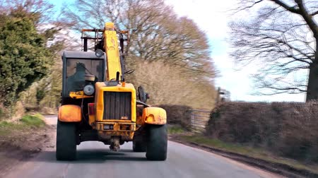 farm equipment : Tractor - POV footage featuring a car following a tractor driving on a country road in Staffordshire, England