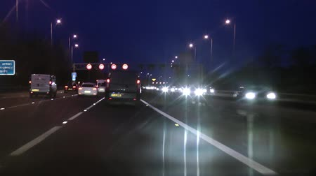 otoyol : POV driving clip of cars on motorway highway M42, M6 Midlands, England at night with bright lights from vehicles and overhead