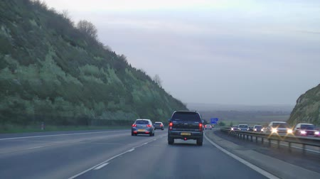 otoyol : POV driving shot of cars on congested motorway highway M40 from London during as the sunsets with blue skies and clouds  Stokenchurch Gap, also known as the Aston Rowant Cutting or Aston Hill cutting