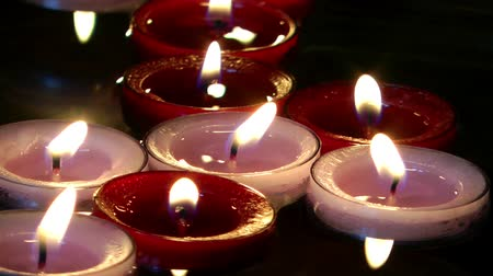 communion : Warm Romantic Floating Red and White Candles Against Dark Background