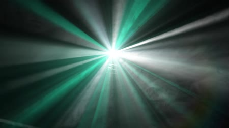 oŚwietlenie : rotating colorful green light rays and fog from movie projector light with lens flares