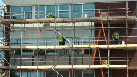 állványzat : Construction workers on scaffolding repairing a building time lapse