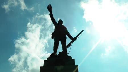 határkő : Silhouette of Soldier World War II memorial against blue sky clouds time lapse - Stafford Town Center, England