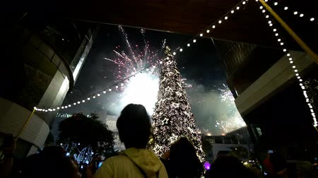 People look up to the sky watching fireworks welcome new year 2018 in front of Central World Bangkok Shopping mall on the first of January 2018 Стоковые видеозаписи