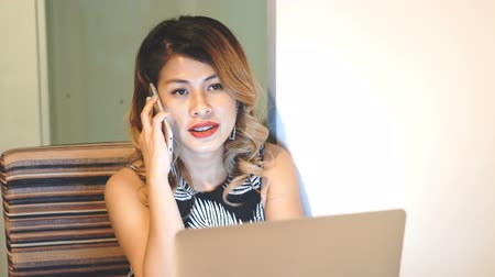 Asian working woman talking on the phone, sitting in front of laptop