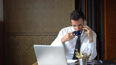 Businessman multitaskin, working, drinking and talking on the phone at the same time