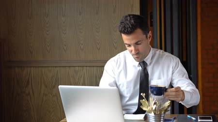 Happy businessman take a sip of coffee while he working