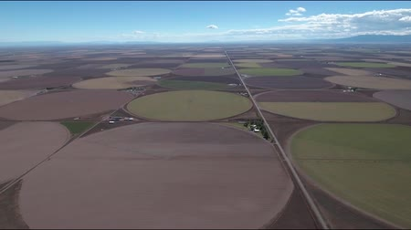 deszcz : High altitude 4K aerial drone wide slow pan of farmland in the San Luis Valley of southern Colorado. The farm land  is surrounded by mountains, the sky is a bright blue and there are a few clouds rolling in. Off in the distance you can see a storm just co