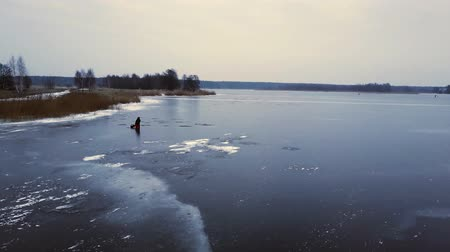 letland : Aerial view on fisherman at a frozen river in Riga, Latvia. 4k footage. Stockvideo
