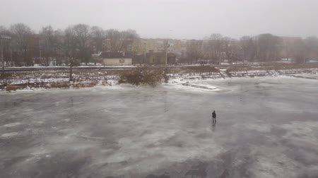 fisher : Aerial view on fisherman at a frozen river in Riga, Latvia. 4k footage. Stock Footage