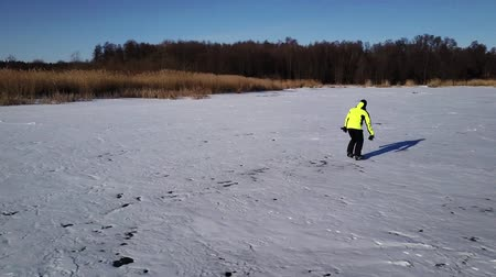 ice skating : Aerial view on skater who is sliding along the frozen ice on river. Drone is following him. Stock Footage