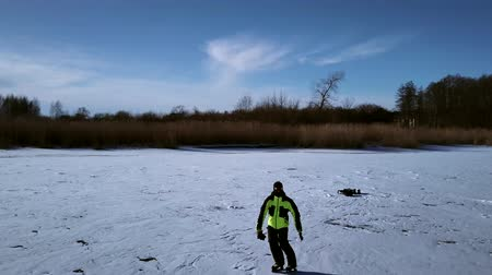 frozen lake : Aerial view on skater who is sliding along the frozen ice on river. Drone is following him. Stock Footage