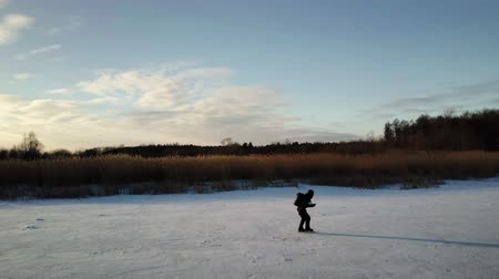 alta calidad : Aerial view on skater who is sliding along the frozen ice on river. Drone is following him. Archivo de Video