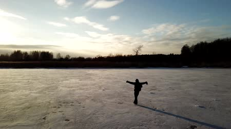 patim : Aerial view: One man is skating on the ice of frozen river during beautiful sunset. Drone is following him and making the video. Vídeos