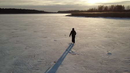 Aerial view on skater who is sliding along the frozen ice on river. Drone is following him. Filmati Stock