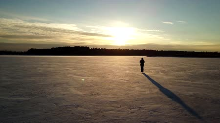 Aerial view: One man is skating on the ice of frozen river during beautiful sunset. Drone is following him and making the video. Filmati Stock