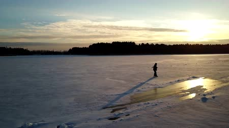 alta calidad : Aerial view: One man is skating on the ice of frozen river during beautiful sunset. Drone is following him and making the video. Archivo de Video