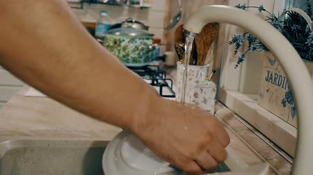 lavatório : Woman washing her hands with soap on kitchen. Close-up view with side camera motion