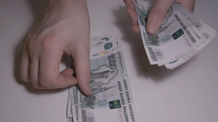 mennyiség : The man counts money Russian ruble over white table slow motion hd footage