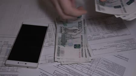 mennyiség : The man counts money Russian ruble over white table for Utility bills pay slow motion hd footage